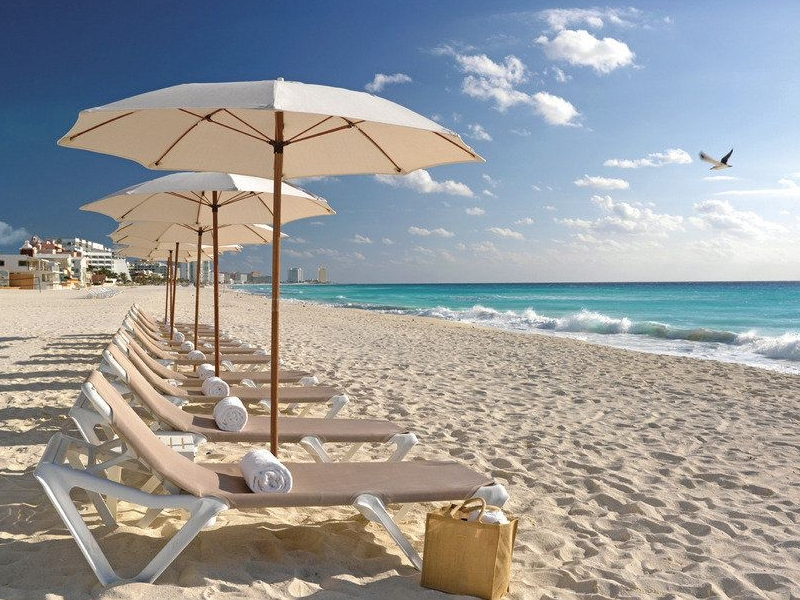 Umbrellas and lounging chairs on the white pristine sand of Cancún beach