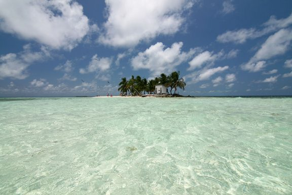 The remote beach of Silk Cayes can be seen from the point of view of a nearing boat that brings visitors